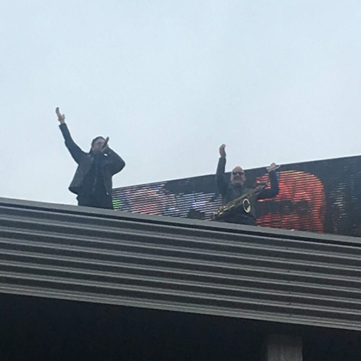 An epic sax guy and a singer on the roof above the podium
