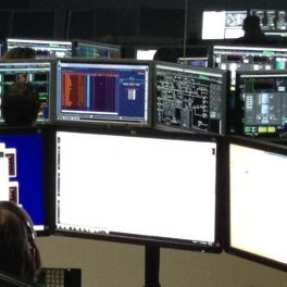 People sitting behind way too many monitors