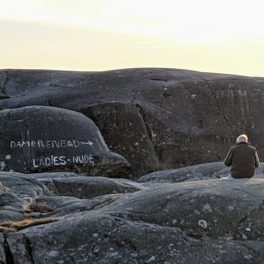 """Man eating sandwiches next to a sign painted on the rocks: """"Ladies nude"""""""